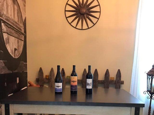 vignoble assortiment de 3 bouteilles de vin sur une table avec un soleil logo du vignoble sur le mur montifalco vineyard ruckersville virginie états unis ulocal produits locaux achat local produits du terroir locavore touriste