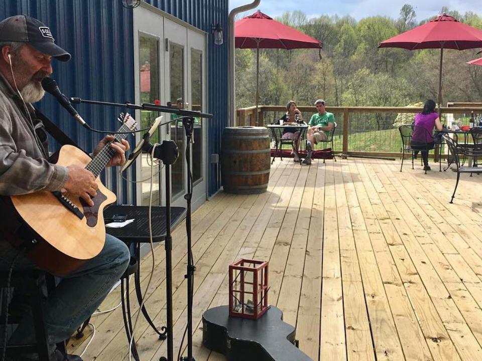 vignoble homme avec sa guitare qui joue de la musique live sur la terrasse avec clients assis aux tables avec vue sur le domaine naked mountain vineyard markham virginie états unis ulocal produits locaux achat local produits du terroir locavore touriste