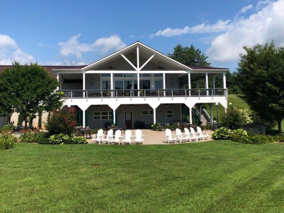 vignoble domaine avec maison blanche luxueuse avec une grande terrasse au 2e étage et patio sous la terrasse avec des chaises adirondack blanche narmada winery amissville virginie états unis ulocal produits locaux achat local produits du terroir locavore touriste