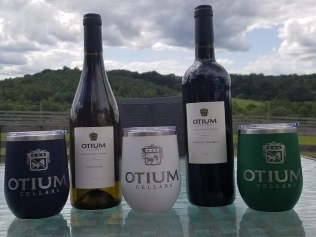 vineyards assortment of 2 bottles of wine and 3 logo glasses on a table in front of the equestrian fences otium cellars purcellville virginia united states ulocal local products local purchase local produce locavore tourist