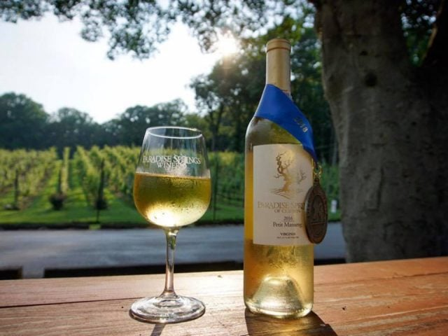 vineyards 482/5000 award-winning bottle of white wine on a table in front of the vines and a mature tree paradise springs winery clifton virginia united states ulocal local products local purchase local produce locavore tourist