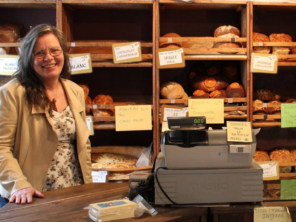 artisan bakeries owner with display of breads boulangerie artisanale grains de vie saint-andré-avellin quebec canada ulocal local products local purchase local produce locavore tourist