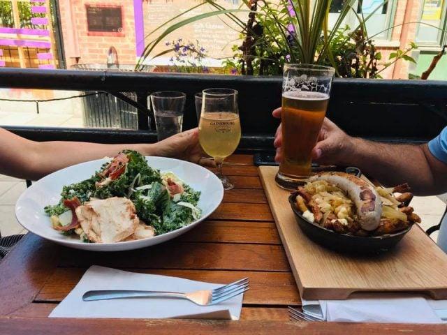 microbrasserie couple à une table sur la terrasse avec 2 plats et bières artisanales gainsbourg bistro brasserie gatineau quebec canada ulocal produits locaux achat local produits du terroir locavore touriste
