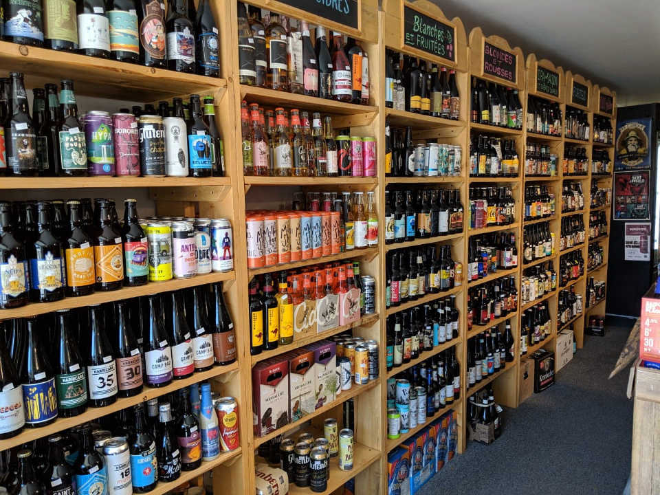 specialty grocery store wall with shelves filled with local beers le brasse-camarade saint-andré-avellin quebec canada ulocal local products local purchase local produce locavore tourist